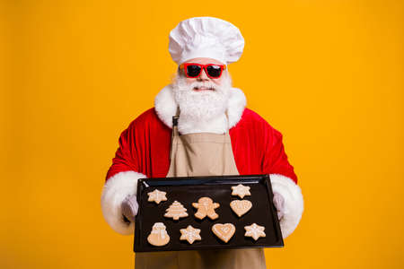 Photo of santa claus chef grandpa grey beard hold ready ginger bread healthy sweets cool grandparent take care kids wear costume gloves sun specs cap apron isolated yellow color background