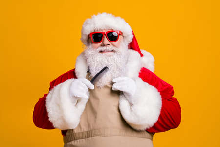 Close-up portrait of his he nice attractive cheerful wee-groomed fat grey-haired Santa wearing apron combing beard beauty salon procedure isolated bright vivid shine vibrant yellow color background