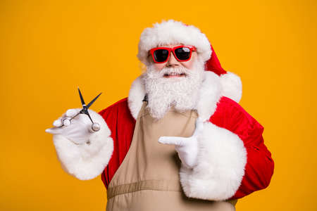 Close-up portrait of his he nice attractive cheerful fat grey-haired Santa father wearing apron demonstrating scissors tool beauty salon isolated bright vivid shine vibrant yellow color background