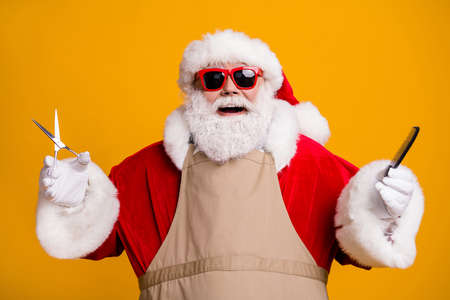 Close-up portrait of nice attractive cheerful cheery glad grey-haired Santa wearing apron holding in hands coiffure tools beauty salon isolated bright vivid shine vibrant yellow color background