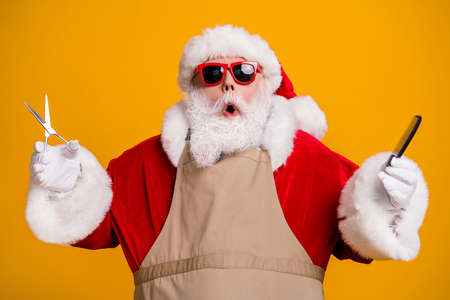 Close-up portrait of nice attractive stunned amazed funny grey-haired Santa wearing apron holding in hands coiffure equipment beauty salon isolated bright vivid shine vibrant yellow color background
