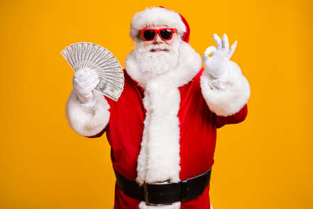 Portrait of his he nice attractive cheerful fat overweight bearded Santa holding in hand cash budget showing ok-sign good job advert isolated bright vivid shine vibrant yellow color background Stock Photo