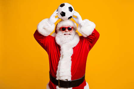 Portrait of his he nice attractive cheerful cheery Santa father holding in hands throwing ball having fun active life isolated over bright vivid shine vibrant yellow color background