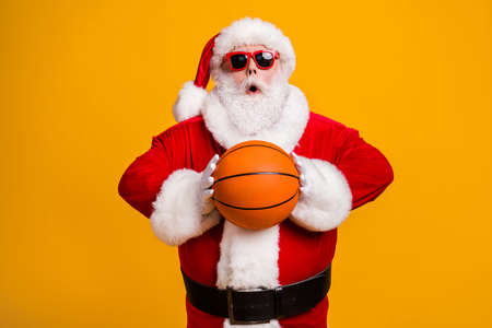 Portrait of his he nice attractive amazed wondered Santa holding in hands throwing orange ball team workout isolated over bright vivid shine vibrant yellow color background