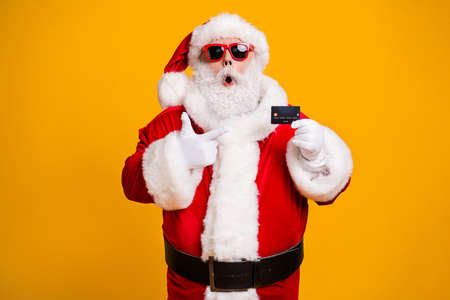 Portrait of his he nice attractive fat amazed astonished Santa holding in hand demonstrating bank card safe shopping novelty isolated bright vivid shine vibrant yellow color background