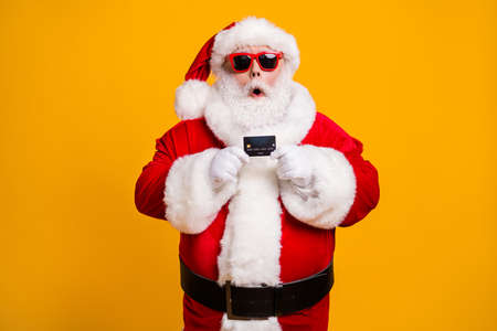 Portrait of his he nice attractive amazed stunned wondered Santa holding in hand bank card budget safe shopping investment isolated bright vivid shine vibrant yellow color background