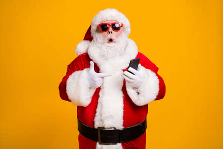Portrait of his he nice attractive amazed fat overweight bearded Santa demonstrating device gadget web service shopping order delivery isolated bright vivid shine vibrant yellow color background