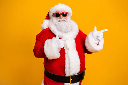 Portrait of his he nice attractive cheerful confident fat Santa demonstrating copy empty blank place space way direction choose choice isolated over bright vivid shine vibrant yellow color background Stock fotó