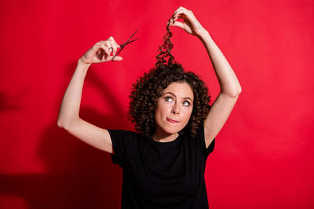 Photo of young doubtful person arm hold scissors trying hard isolated on bright red color background