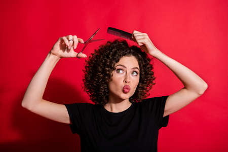 Photo of nice young person hold scissors brush look empty space isolated on vivid red color background