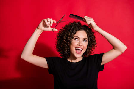 Portrait of toothy beautiful lady professional stylist hold scissors brush cut hair isolated on red color background