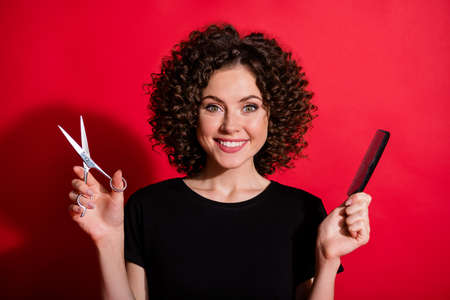 Photo of nice young girl smile hands holding scissors brush ready to cut isolated on bright red color background 版權商用圖片