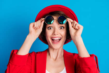 Close-up portrait of pretty amazed cheerful lady touching specs great good news reaction isolated on bright vivid blue color background
