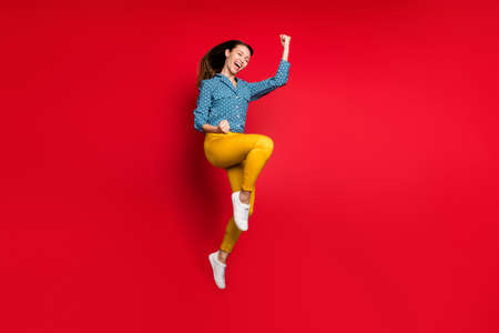 Full length body size view of pretty overjoyed cheerful girl jumping having fun rejoicing isolated bright red color background Фото со стока