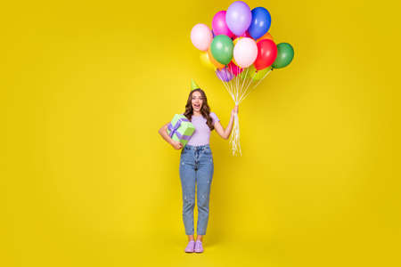 Full length body size view of attractive amazed cheerful wavy-haired girl holding bunch balls isolated bright yellow color background