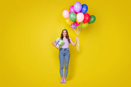 Full length body size view of pretty cheerful wavy-haired girl holding bunch balls congrats isolated bright yellow color background