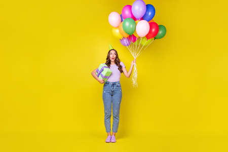 Full length body size view of attractive amazed glad cheery wavy-haired girl holding giftbox balls isolated bright yellow color background