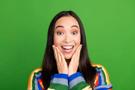 Close-up portrait of pretty amazed delighted cheerful girl enjoying great news isolated over bright green color background