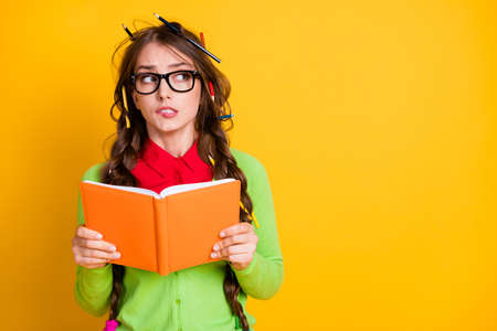 Portrait of attractive funky nervous teenage girl reading exercise book thinking biting lip copy space isolated over bright yellow color background