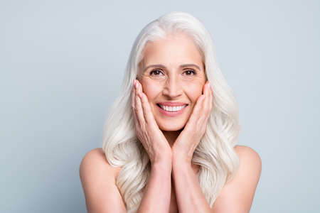 Close-up portrait of her she nice attractive cheerful grey-haired elderly lady touching silky skin cleansing isolated on gray pastel color background