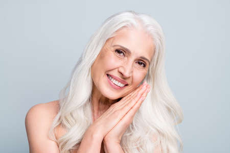 Close up photo of beautiful aged white hair lady apply daily night cream arms near cheek isolated grey color background