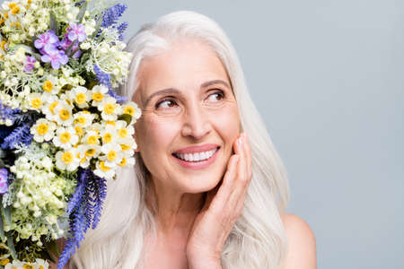 Photo of beautiful retired woman stand near big bunch wild flowers touch cheek look empty space isolated grey color background