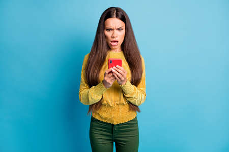 Photo portrait of upset woman holding red phone in two hands with open mouth isolated on pastel blue colored background