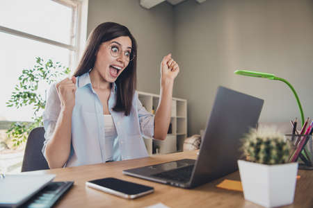Photo of crazy excited girl raise fists open mouth look screen laptop wear spectacles shirt in home office indoors