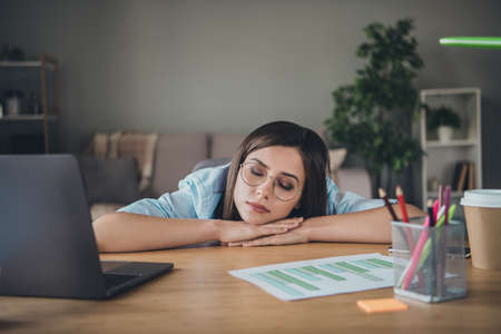 Photo of sleepy pretty girl head cozy lay hands closed eyes wear glasses shirt in home office indoors