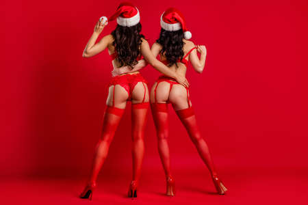 Full length body size rear back behind view of two nice attractive seductive tempting hot girls wear claus hat embracing posing isolated bright vivid shine vibrant red color background