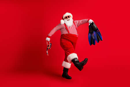 Full length photo of grandfather grey beard go hold blue gear mask fins wear santa claus x-mas costume suspenders sunglass striped shirt cap boots isolated red color background