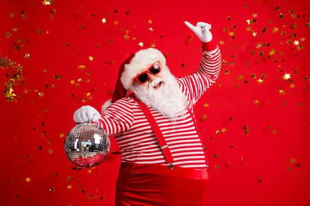 Photo of pensioner old man grey beard hold retro disco ball dance raise finger wear santa x-mas costume suspenders sunglass gloves striped shirt cap isolated red color background