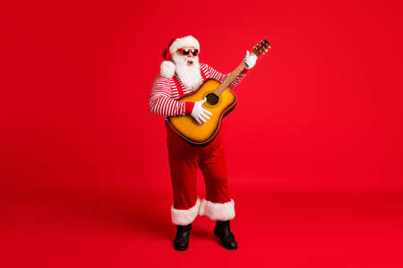 Full length body size view of his he handsome cheery Santa gather vocalist soloist playing solo guitar singing hit having fun vocal voice isolated bright vivid shine vibrant red color background Stock Photo