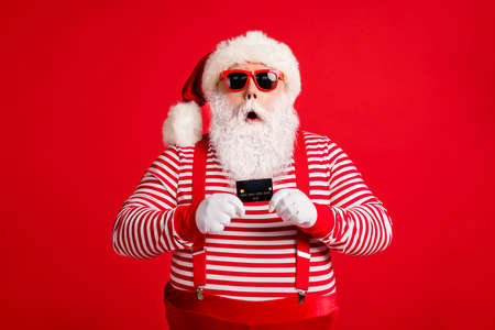 Portrait of his he nice handsome amazed stunned wondered bearded fat Santa holding in hand bank card modern novelty service reaction isolated over bright vivid shine vibrant red color background