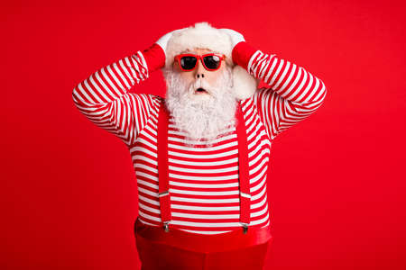 Portrait of his he nice handsome attractive wondered amazed grey-haired Santa festal bargain reaction isolated over bright vivid shine vibrant red color background