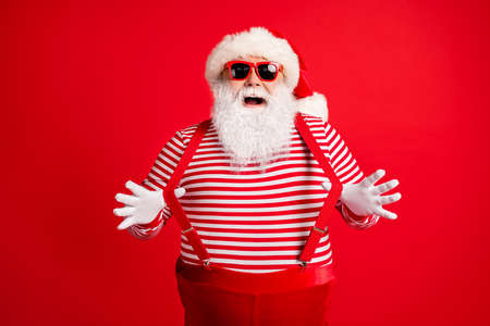 Portrait of his he nice handsome attractive comic childish cheerful cheery grey-haired Santa wearing gloves having fun pulling suspenders isolated over bright vivid shine vibrant red color background