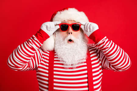 Close-up portrait of his he nice handsome amazed stunned grey-haired Santa wearing touching sunglasses winter bargain reaction isolated over bright vivid shine vibrant red color background