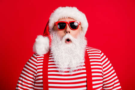 Close-up portrait of his he nice handsome attractive amazed stunned white-haired Santa christmastime sale wearing sunglasses isolated over bright vivid shine vibrant red color background