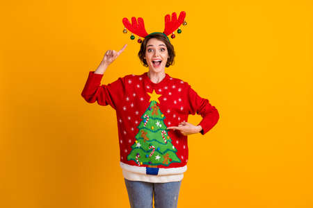 Photo of amazed positive girl point finger deer headband christmas tree decor pullover x-mas noel theme party gift isolated over bright shine color background