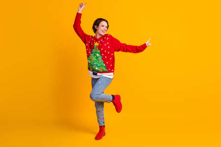 Full size photo of positive cheerful girl dance x-mas newyear party wear christmas tree decor sweater boots denim isolated over bright shine yellow color background