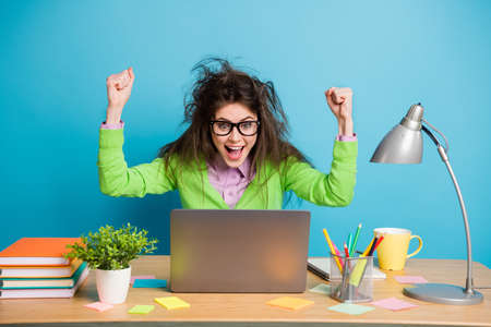 Portrait of delighted girl sit table study remote laptop raise fists scream isolated blue color background Stockfoto