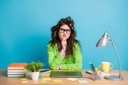 Uncertain pencil hairstyle girl sit table touch fingers chin look copyspace think isolated blue color background