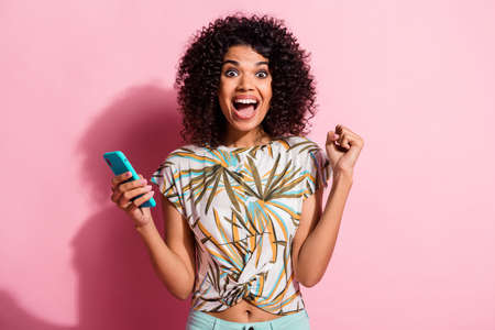 Photo portrait of celebrating woman holding phone in one hand with fist in air isolated on pastel pink colored background