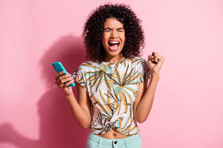 Photo portrait of screaming woman celebrating holding phone in one hand with fist in air isolated on pastel pink colored background Stockfoto