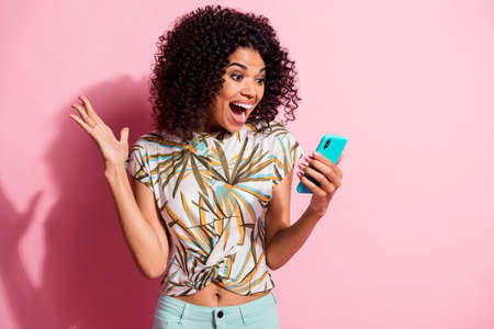 Photo portrait of shocked screaming girl unexpectedly winning holding phone in hand isolated on pastel pink colored background Stockfoto