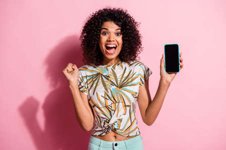 Photo portrait of celebrating woman holding phone with blank space in one hand isolated on pastel pink colored background