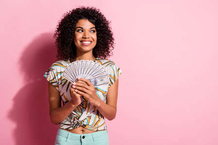 Portrait photo of black skinned curly curious girl keeping showing money looking at blank space isolated on pastel pink color background
