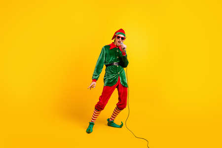 Full length body size view of his he nice attractive cool talented famous funny guy elf star mc singing hit having fun celebratory isolated over bright vivid shine vibrant yellow color background Foto de archivo