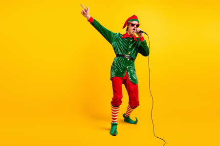 Full length body size view of his he nice attractive cool talented funny guy elf mc pj dj singing hit having fun festal day isolated over bright vivid shine vibrant yellow color background Foto de archivo