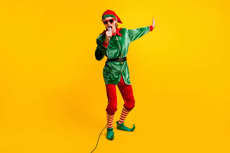 Full length body size view of his he nice attractive cheerful popular talented funny guy elf singing hit having fun Eve Noel isolated over bright vivid shine vibrant yellow color background